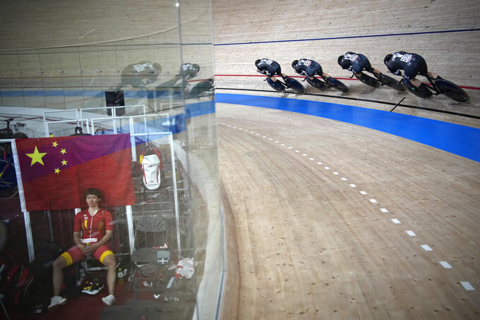 Team New Zealand competes while Tianshi Zhong of Team China, left, takes a break during a qualifying heat for track cycling women's team pursuit at the 2020 Summer Olympics, Monday, Aug. 2, 2021, in Izu, Japan. (AP Photo/Christophe Ena)