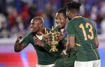 South Africa's Makazole Mapimpi, left, and Lukhanyo Am, right, celebrate with the Webb Ellis Cup after their win over England in the Rugby World Cup final at International Yokohama Stadium in Yokohama, Japan, Saturday, Nov. 2, 2019. (AP Photo/Aaron Favila)
