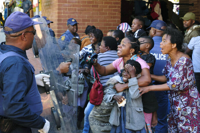 Refugees, mostly from the Democratic Republic of Congo, face off with South African Police officers, at the United Nations High Commissioner for Refugees (UNHCR) compound in Pretoria, South Africa, Friday, Nov. 15, 2019. Police removed about 150 refugees who the United Nations refugee agency says forced their way into its compound while protesting recent anti-immigrant attacks. (AP Photo/Elna Schütz)