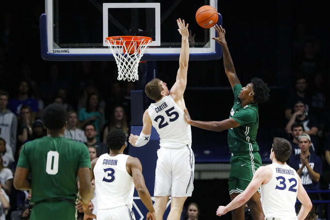 Jacksonville's Bryce Workman, right, shoots against Xavier's Jason Carter (25) during the second half of an NCAA college basketball game Tuesday, Nov. 5, 2019, in Cincinnati. (AP Photo/John Minchillo)
