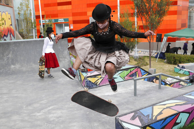 """Aide Choque, wearing a mask amid the COVID-19 pandemic, jumps with her skateboard during a youth talent show in La Paz, Bolivia, Wednesday, Sept. 30, 2020. Young women called """"Skates Imillas,"""" using the Aymara word for girl Imilla, use traditional Indigenous clothing as a statement of pride of their Indigenous culture when riding their skateboards. (AP Photo/Juan Karita)"""