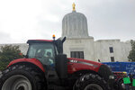 A convoy of trucks and tractors circle the Oregon state Capitol on Thursday, June 27, 2019 in Salem, Ore. Protesters are supporting the eleven Republican senators who walked out over a week ago to avoid a vote on climate legislation. (AP Photo/Sarah Zimmerman)