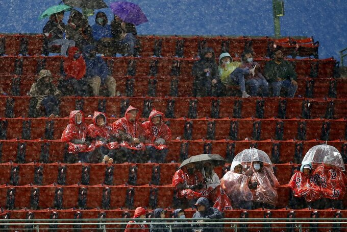Fans sit in the rain during the third inning of a baseball game between the Boston Red Sox and the Miami Marlins, Friday, May 28, 2021, in Boston. (AP Photo/Michael Dwyer)