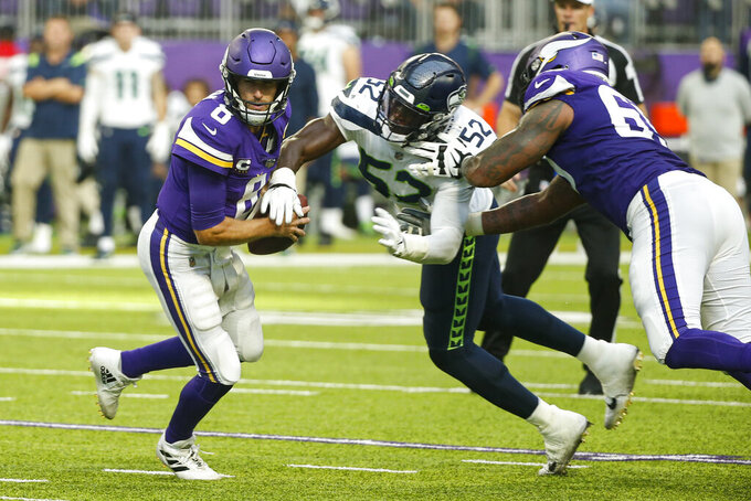Seattle Seahawks defensive end Darrell Taylor (52) strips the ball from Minnesota Vikings quarterback Kirk Cousins (8) in the second half of an NFL football game in Minneapolis, Sunday, Sept. 26, 2021. Cousins recovered the ball. (AP Photo/Bruce Kluckhohn)