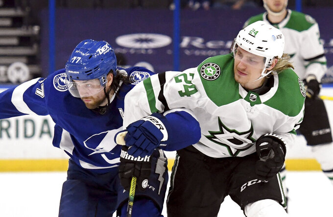 Tampa Bay Lightning defenseman Victor Hedman (77) and Dallas Stars left wing Roope Hintz (24) fight for position during the third period of an NHL hockey game Friday, May 7, 2021, in Tampa, Fla. (AP Photo/Jason Behnken)
