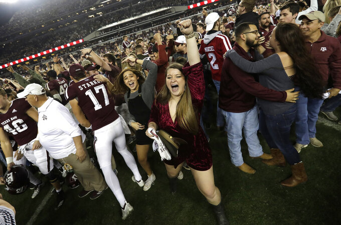 Students and fans celebrate with Texas A&M football players after an NCAA college football game against LSU Saturday, Nov. 24, 2018, in College Station, Texas. Texas A&M won 74-72 in the seventh overtime. (AP Photo/David J. Phillip)