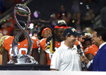 Clemson head coach Dabo Swinney, center in white, gives a broadcast interview as he and his team celebrate their 30-3 win against Notre Dame in the NCAA Cotton Bowl semi-final playoff football game, Saturday, Dec. 29, 2018, in Arlington, Texas. Clemson won 30-3. (AP Photo/Jeffrey McWhorter)