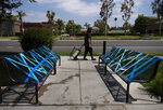 A woman walks past benches taped off for social distancing outside a restaurant, Thursday, July 2, 2020, in La Habra, Calif. California's mood has gone from optimistic to sour as coronavirus cases and hospitalizations are on the rise heading into the July 4th weekend. Gov. Gavin Newsom has ordered bars and indoor restaurant dining closed in most of the state, many beaches are off limits, and he's imploring Californians to avoid holiday gatherings with family and friends. (AP Photo/Jae C. Hong)