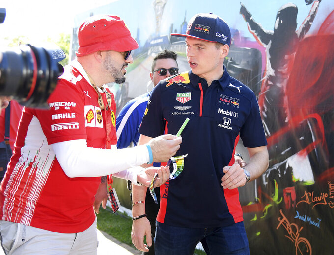 Red Bull driver Max Verstappen of the Netherlands, right, declines an autograph for a fan as he arrives at the track for the Australian Formula One Grand Prix in Melbourne, Thursday, March 12, 2020. (AP Photo/Andy Brownbill)