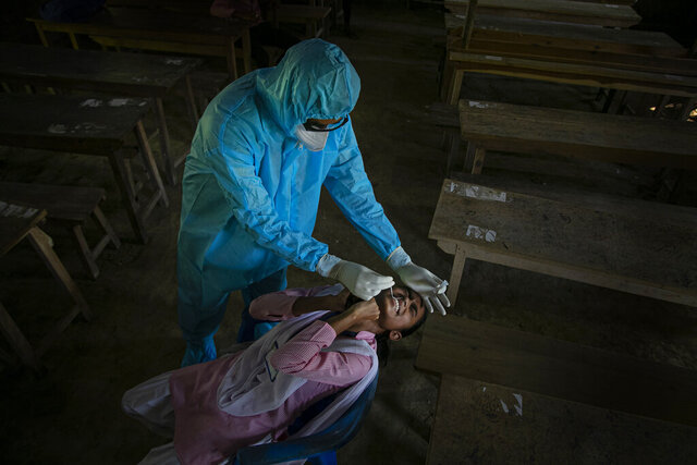 An Indian health worker takes a nasal swab sample of a student to test for coronavirus after classes started at a college in Jhargaon village, outskirts of Gauhati, India, Wednesday, Sept. 30, 2020. India's Health Ministry on Wednesday raised its confirmed total of coronavirus cases to more than 6.2 million. (AP Photo/Anupam Nath)