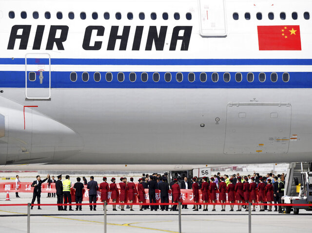 FILE - In this May 13, 2019, file photo, airline crew members gather near the underbelly of an Air China passenger jet during an event at the Beijing Daxing International Airport. Air China is seeking to reduce flights to the United States and offer unusual legs between U.S. cities because of a drop-off in travel and new restrictions on people entering the U.S. from China due to the coronavirus outbreak. (Chinatopix Via AP, File)