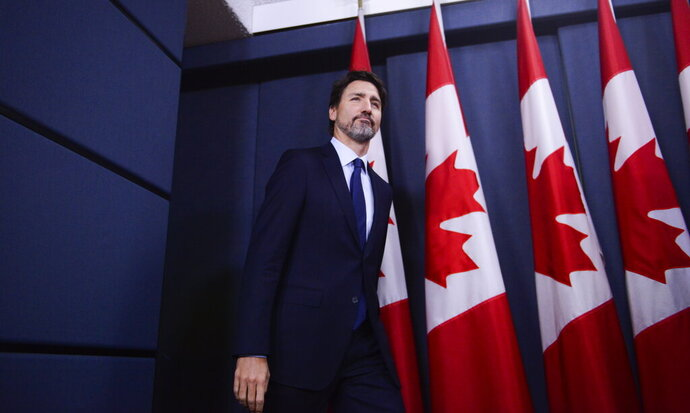 Canada Prime Minister Justin Trudeau arrives at a press conference at the National Press Theatre in Ottawa, Friday, Jan. 17, 2020. Trudeau said Friday his government will give $25,000 Canadian ($19,122 U.S.) to families of each of the 57 citizens and 29 permanent residents of Canada who perished in the downing of a Ukrainian jetliner in Iran last week. (Sean Kilpatrick/The Canadian Press via AP)