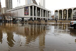 New York's Lincoln Center for the Performing Arts is reflected in a flooded street, in New York, Monday, Jan. 13, 2020. A water main break flooded streets on Manhattan's Upper West Side near Lincoln Center and hampered subway service during the Monday morning rush hour. (AP Photo/Richard Drew)