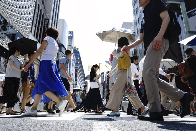 In this July 20, 2018, photo, people walk on a street in Ginza shopping district in Tokyo. Japan reports its economy resumed its longtime expansion in the last quarter as consumers and businesses stepped up spending. (AP Photo/Eugene Hoshiko)