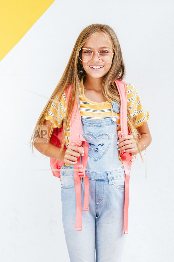 Smiling girl carrying backpack while standing in front of wall