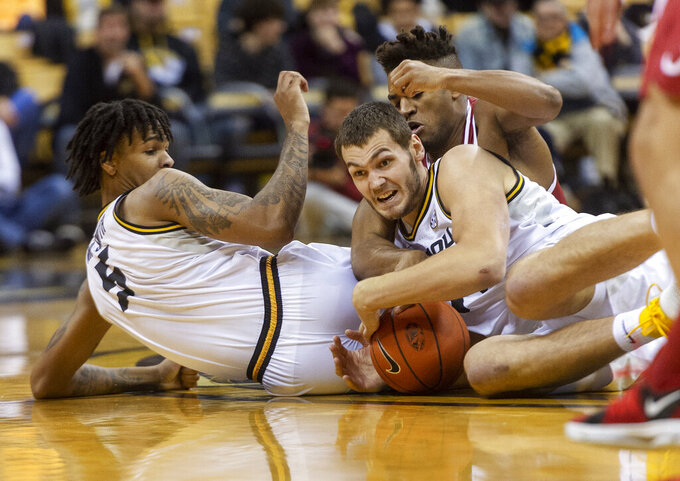Missouri's Reed Nikko, center, holds on to the ball between teammate Mitchell Smith, left, and Alabama's Avery Johnson Jr., right, during the first half of an NCAA college basketball game, Wednesday, Jan. 16, 2019, in Columbia, Mo. (AP Photo/L.G. Patterson)