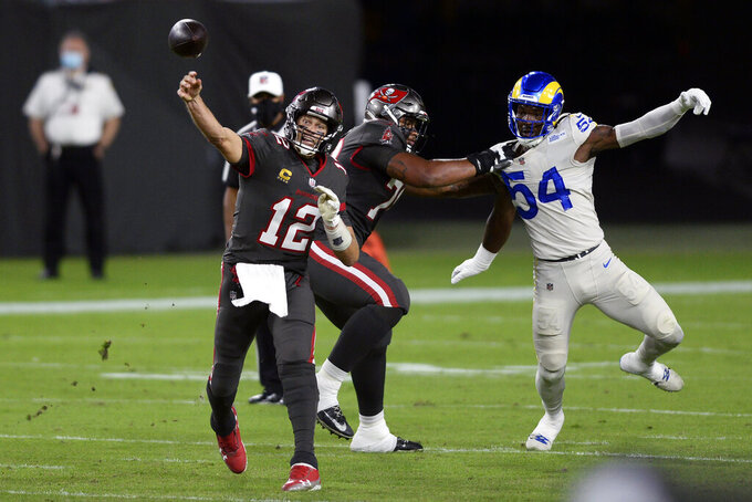 Tampa Bay Buccaneers quarterback Tom Brady (12) throws a pass as offensive tackle Tristan Wirfs (78) blocks Los Angeles Rams outside linebacker Leonard Floyd (54) during the first half of an NFL football game Monday, Nov. 23, 2020, in Tampa, Fla. (AP Photo/Jason Behnken)