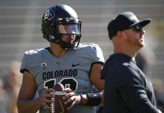 Colorado quarterback Steven Montez warms up as assistant coach Darrin Chiaverini looks on before an NCAA college football game against Air Force, Saturday, Sept. 14, 2019, in Boulder, Colo. (AP Photo/David Zalubowski)