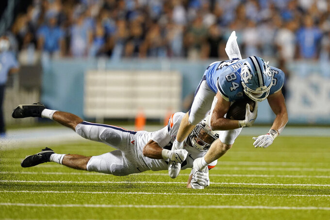 Virginia free safety Joey Blount, left, reaches to tackle North Carolina tight end Garrett Walston (84) during the second half of an NCAA college football game in Chapel Hill, N.C., Saturday, Sept. 18, 2021. (AP Photo/Gerry Broome)