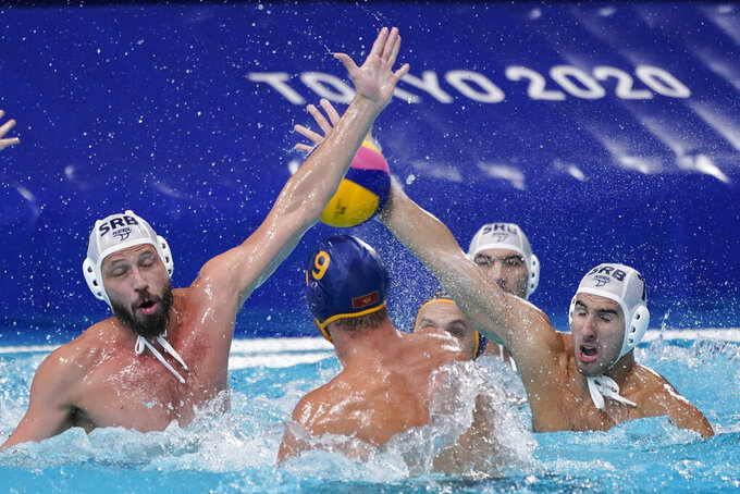Serbia's Strahinja Rasovic, right, blocks a shot by Montenegro's Aleksandar Ivovic (9) during a preliminary round men's water polo match at the 2020 Summer Olympics, Monday, Aug. 2, 2021, in Tokyo, Japan. (AP Photo/Mark Humphrey)