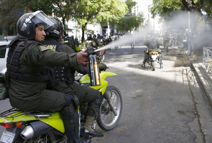 A police officer sprays pepper spray at anti-government demonstrators during a protest against the reelection of President Evo Morales, in La Paz, Bolivia, Tuesday, Oct. 29, 2019. Morales' backers and foes are blocking streets and highways across the country in a dispute over official election results that show him winning reelection without a runoff. (AP Photo/Juan Karita)