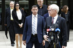 California Republican Rep. Duncan Hunter, center, walks out of federal court Tuesday, Dec. 3, 2019, in San Diego. Hunter gave up his year-long fight against federal corruption charges and pleaded guilty Tuesday to misusing his campaign funds, paving the way for the six-term Republican to step down. (AP Photo/Gregory Bull)
