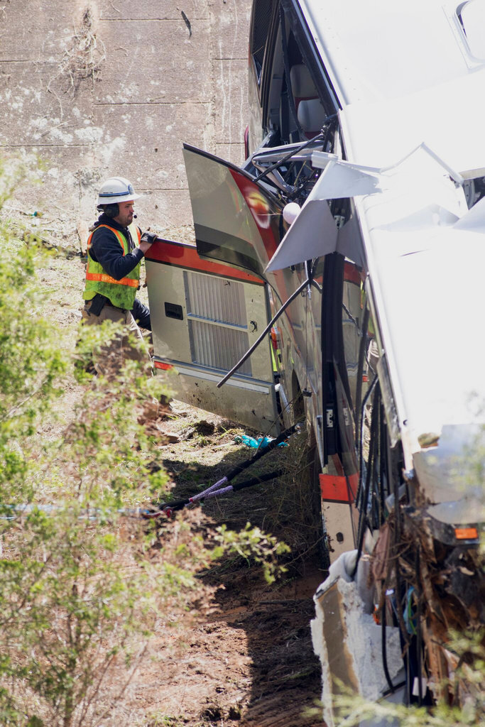 Emergency personnel looks into a bus that crashed into a ravine in Loxley, Ala., Tuesday, March 13, 2018. The bus carrying dozens of students and six adults from Channelview crashed early Tuesday on Interstate 10 near the Alabama-Florida line. The driver died and about three dozen others went to hospitals.  (Gregg Pachkowski/Pensacola News Journal via AP)