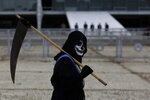 A demonstrator dressed as death and wearing a mock presidential sash walks outside Planalto presidential palace during a protest against the president's handling of the COVID-19 pandemic in Brasilia, Brazil, Friday, March 19, 2021. (AP Photo/Eraldo Peres)