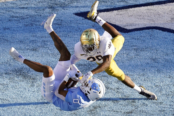 North Carolina wide receiver Emery Simmons (0) catches a touchdown pass as Notre Dame cornerback TaRiq Bracy (28) defends during the first half of an NCAA college football game in Chapel Hill, N.C., Friday, Nov. 27, 2020. (AP Photo/Gerry Broome)