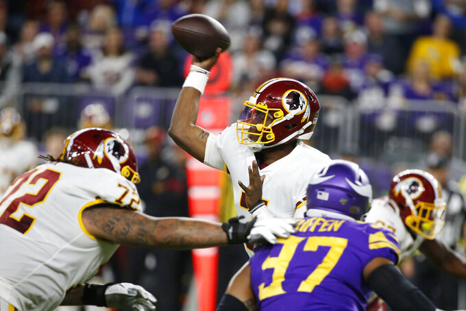 Washington Redskins quarterback Dwayne Haskins, center, throws a pass during the second half of an NFL football game against the Minnesota Vikings, Thursday, Oct. 24, 2019, in Minneapolis. (AP Photo/Bruce Kluckhohn)