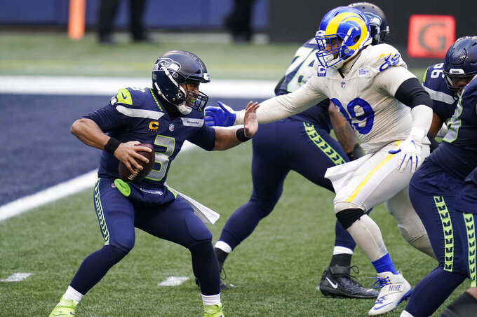 Seattle Seahawks quarterback Russell Wilson (3) tries to fend off a sack by Los Angeles Rams defensive lineman Aaron Donald (99) during the second half of an NFL football game, Sunday, Dec. 27, 2020, in Seattle. (AP Photo/Elaine Thompson)