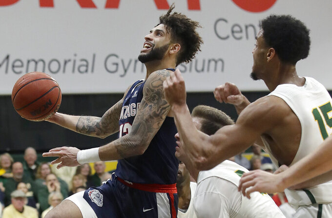 Gonzaga guard Josh Perkins, left, shoots against San Francisco guard Frankie Ferrari, bottom, and forward Nate Renfro (15) during the first half of an NCAA college basketball game in San Francisco, Saturday, Jan. 12, 2019. (AP Photo/Jeff Chiu)