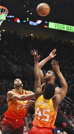 Portland Trail Blazers forward Evan Turner shoot over Utah Jazz center Rudy Gobert, left, and guard Donovan Mitchell (45) during the first half of an NBA basketball game in Portland, Ore., Wednesday, April 11, 2018. (AP Photo/Steve Dykes)
