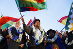 Bolivia's President Evo Morales waves flags before supporters as he celebrates his reelection, alongside Vice President Alvaro Garcia Linera in El Alto, Bolivia, Monday, Oct. 28, 2019. Morales' backers and foes are blocking streets and highways across the country in a dispute over official election results that show the leftist leader winning reelection without a runoff. (AP Photo/Juan Karita)