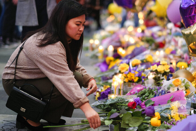 A fan places flowers at a memorial for Kobe Bryant near Staples Center, Monday, Jan. 27, 2020, in Los Angeles. Bryant, the 18-time NBA All-Star who won five championships and became one of the greatest basketball players of his generation during a 20-year career with the Los Angeles Lakers, died in a helicopter crash Sunday. (AP Photo/Ringo H.W. Chiu)