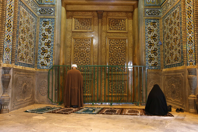 A cleric and a woman pray behind a closed door of Masoume shrine in the city of Qom, some 80 miles (125 kilometers) south of the capital Tehran, Iran, Monday, March 16, 2020. On Monday, Iran closed the Masoume shrine, a major pilgrimage site in the city of Qom, the epicenter of the country's new coronavirus outbreak. Authorities were already restricting access and barring pilgrims from kissing or touching the shrine, but it had remained open. (AP Photo)