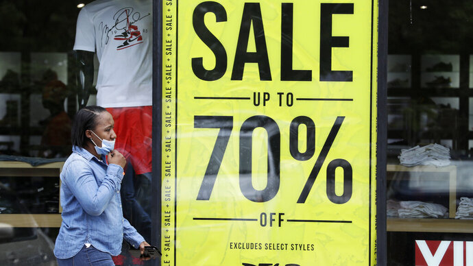 A woman walks past a store advertising sales at 70 percent off, Thursday, May 21, 2020, in Cleveland. More than 2.4 million people applied for U.S. unemployment benefits last week in the latest wave of layoffs from the viral outbreak that triggered widespread business shutdowns two months ago and sent the economy into a deep recession. (AP Photo/Tony Dejak)