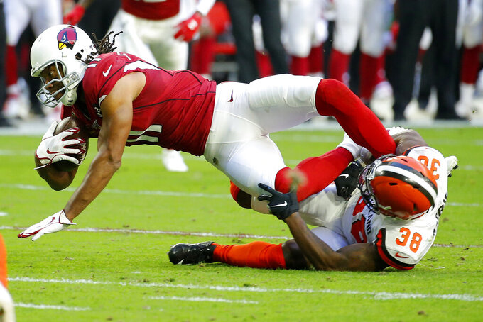 Arizona Cardinals wide receiver Larry Fitzgerald is tackled by Cleveland Browns defensive back T.J. Carrie (38) during the first half of an NFL football game, Sunday, Dec. 15, 2019, in Glendale, Ariz. (AP Photo/Rick Scuteri)