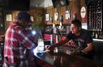 Daniel Ibarra, right, gives a manually written receipt to customer Mark Costales, who paid for lunch in cash, at Murphy's Irish Pub & Restaurant, in Sonoma, Calfi., Wednesday, Oct. 9, 2019. Pacific Gas & Electric has cut power to more than half a million customers in Northern California hoping to prevent wildfires during dry, windy weather throughout the region. (Christopher Chung/The Press Democrat via AP)