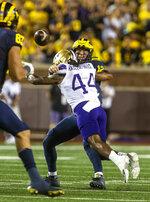 Washington defensive back Brendan Radley-Hiles (44) tackles Michigan quarterback Cade McNamara (12) in the first quarter of an NCAA college football game in Ann Arbor, Mich., Saturday, Sept. 11, 2021. (AP Photo/Tony Ding)