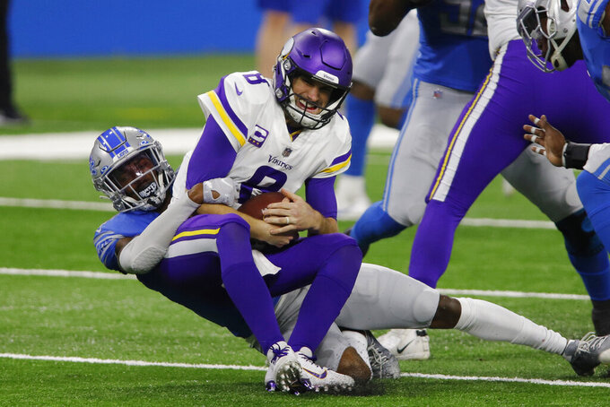 Minnesota Vikings quarterback Kirk Cousins (8) is sacked by Detroit Lions defensive back Tracy Walker during the first half of an NFL football game, Sunday, Jan. 3, 2021, in Detroit. (AP Photo/Al Goldis)