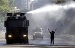"A protester holds her hands up toward a police truck spraying a water canon at students and union members marching in Santiago, Chile, Monday, Oct. 21, 2019. Hundreds of protesters defied an emergency decree and confronted police in Chile's capital on Monday, continuing disturbances that have left at least 11 dead and led the president to say the country is ""at war."" (AP Photo/Miguel Arenas)"