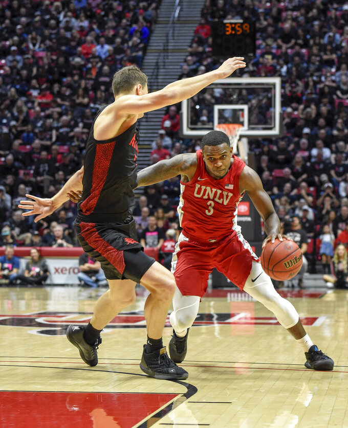 UNLV guard Amauri Hardy (3) drives past the defense of San Diego State forward Yanni Wetzell, left, during the second half of an NCAA college basketball game Saturday, Feb. 22, 2020, in San Diego. (AP Photo/Denis Poroy)