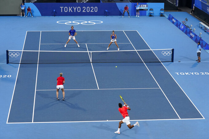 Felix Auger-Aliassime, bottom right, and Gabriela Dabrowski, of Canada, return to Stefanos Tsitsipas, top left, and Maria Sakkari, of Greece, during a first round mixed doubles tennis match at the 2020 Summer Olympics, Wednesday, July 28, 2021, in Tokyo, Japan. (AP Photo/Patrick Semansky)