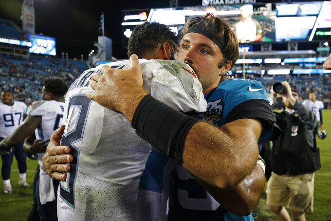 Tennessee Titans quarterback Marcus Mariota, left, and Jacksonville Jaguars quarterback Gardner Minshew greet each other after during an NFL football game, Thursday, Sept. 19, 2019, in Jacksonville, Fla. (AP Photo/Stephen B. Morton)