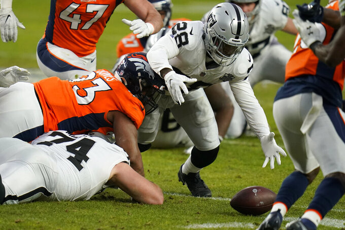 Las Vegas Raiders running back Josh Jacobs (28) recovers his own fumble against the Denver Broncos during the first half of an NFL football game, Sunday, Jan. 3, 2021, in Denver. (AP Photo/Jack Dempsey)