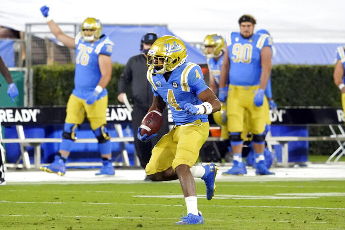 UCLA defensive back Stephan Blaylock (4) runs back after intercepting a pass against Arizona during the second half of an NCAA college football game Saturday, Nov. 28, 2020, in Pasadena, Calif. (AP Photo/Marcio Jose Sanchez)