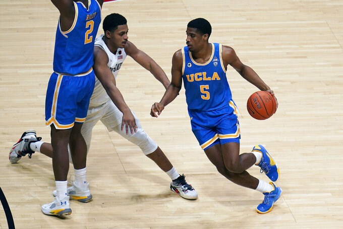 UCLA guard Chris Smith (5) drives to the basket as San Diego State forward Matt Mitchell (11) defends, center, during the first half of an NCAA college basketball game Wednesday, Nov. 25, 2020, in San Diego. (AP Photo/Gregory Bull)