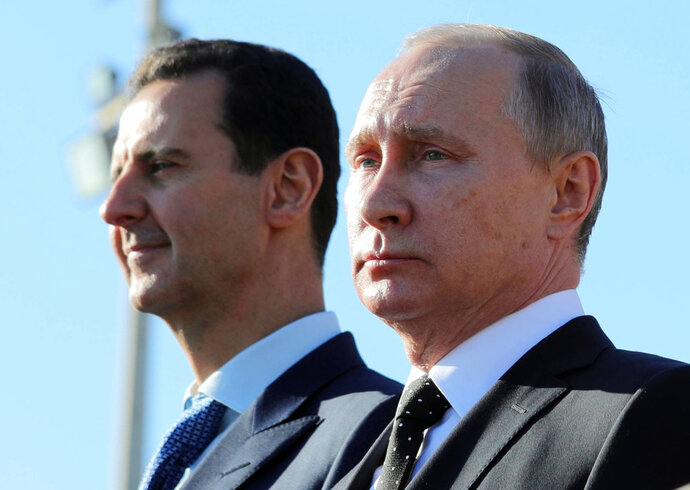 FILE - This Dec. 11, 2017 file photo, shows Russian President Vladimir Putin, right, and Syrian President Bashar Assad watching troops march at the Hemeimeem air base in Syria. In comments published on the official presidency Telegram channel Wednesday, March 14, 2018, Assad said his country's war on terrorism will continue as long as there is
