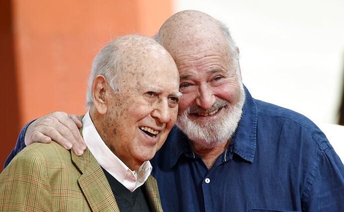 """FILE - In this April 7, 2017 file photo, Carl Reiner, left, and his son Rob Reiner pose together following their hand and footprint ceremony at the TCL Chinese Theatre in Los Angeles. Carl Reiner, the ingenious and versatile writer, actor and director who broke through as a """"second banana"""" to Sid Caesar and rose to comedy's front ranks as creator of """"The Dick Van Dyke Show"""" and straight man to Mel Brooks' """"2000 Year Old Man,"""" has died, according to reports. Variety reported he died of natural causes on Monday night, June 29, 2020, at his home in Beverly Hills, Calif. He was 98. (Photo by Chris Pizzello/Invision/AP, File)"""